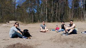 Fyra unga personer med ett litet barn och en hund sitter på sandstranden och njuter av vårsolen.