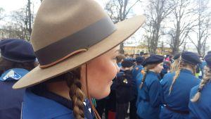 En scoutflicka med en bred filthatt i en samling med många andra scouter.