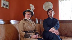Nina Gran och Fabian Silén poserar i sina roller som fröken Lindholm och pastor Petrell i en tidig 1900-talsmiljö.