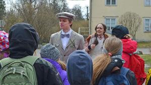 Edvin Eliasson (Elias Edström) tilltalar en barnaskara framför Hertonäs gård, med en piga i bakgrunden.
