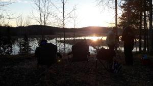 Luontotoimittajat ovat asetelleen retkituoleja järven rannalle. Aurinko nousee.