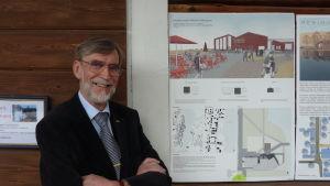 Christer Norrvik står bredvid en plansch av vinnarbidraget i arkitekttävlingen.