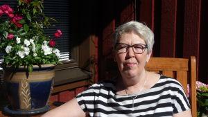 Marianne Nyqvist-Mannsén sitter vid ett bord med en blomkruka på.