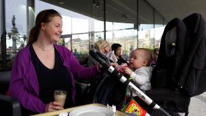 Cecilia på café, med latte i handen, baby tittar nyfiket ut ur vagnen
