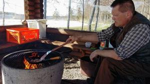 Stefan Pellas steker en kolbulle över öppen eld.
