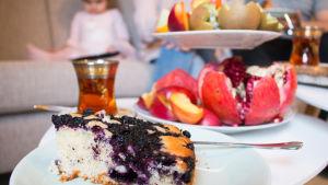Pöytä, jolla on hedelmäasetelma ja mustikkapiirakkaa