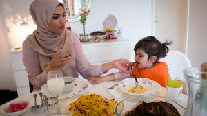 Huivipäinen äiti syöttää lasta ruokapöydässä