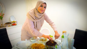 Huivipäinen nainen kattaa ruokaa pöytään