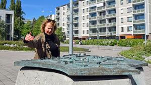 Laura Kolbe står vid en miniatyr av stadsdelen Rönnbacka.