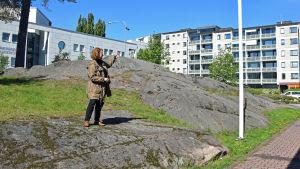 Laura Kolbe står på en bergsknall och pekar på ett höghus.