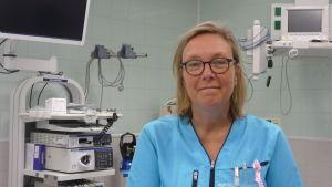 Mia Vanhatalo poserar framför en hel del sjukhusapparater.