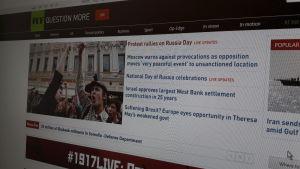 """En bild av första sidan på tv-kanalen och nyhetssajten RT, med texten """"Question more"""" som slogan som syns uppe till vänster."""