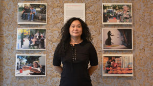 Chyia Chias som sytår mellan sina tavlor i Runebergs hemmet