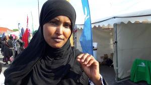 Fadumo said i svart niqab, med ena handen höjd, som i ett samtal. Partitält i bakgrunden.
