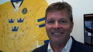 Lennart Käll leende, framför en svensk hockeylandslagströja med autografer
