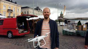 Jonatan Hedberg håller upp sin drönare på Salutorget i Helsingfors.