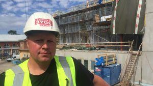 En man står framför en byggarbetsplats.