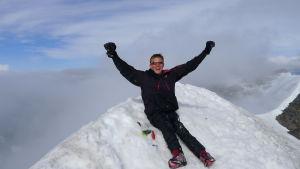 Aron Anderson sitter på toppen av Kebnekaise. Bergskammar syns i bakgrunden.