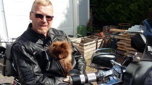 Thomas Wikholm iklädd svart läderjacka. Sitter på en motorcykel. Innanför läderjackan ser man hunden Demi, en liten brun hund av rasen pomeranian.