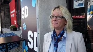 Carina Herrstedt i profil framför SD-logga på husfasad.