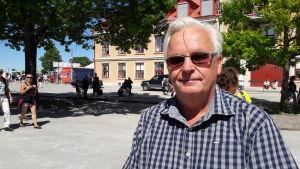 Tommy Gardell, i solglasögon och rutig skjorta, på solig gata i Visby.