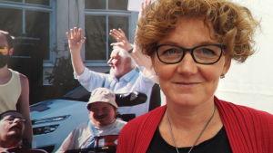 Cecilia Blanck framför affisch med medlemmar inom JAG, som skrattar och sträcker händerna glatt upp i luften.