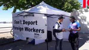 Don´t Deport Foreign Workers står på ett tält där två aktivister delar ut flygblad,