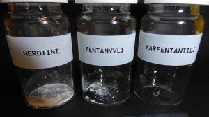 Tre glasburkar innehållandes en dödlig dos av heroin, fentanyl respektive karfentanil.