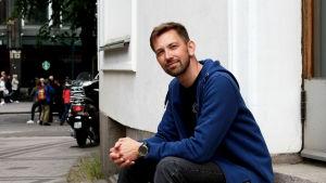 Anders Ahlbäck sitter på en trappa.