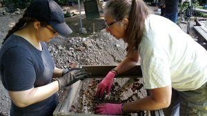Arkeologen Elina Mattila och Hanna-Maija Saarimaa sållar jord för att hitta eventuella fynd i en arkeologisk utgrävning vid museet Aboa Vetus & Ars Nova.