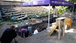 Arkoelogen Ilari Aalto övervakar frivilliga vid utgrävning i en grop vid museet Aboa Vetus & Ars Nova.
