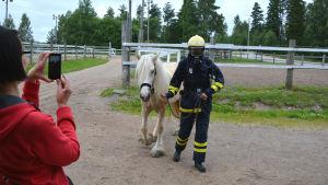 Man i brandutrustning leder häst, kvinna i rött fotograferar