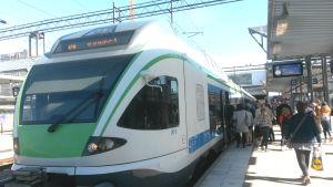 Ett lokaltåg har stannat vid en perrong och passagerare stiger på.