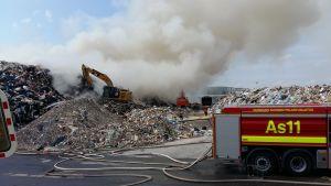 Brandbil och grävmaskiner vid en stor avfallshög som brinner.