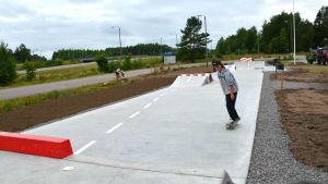 Skejtare åker mot kameran. I bakgrunden synns lång grå betongramp