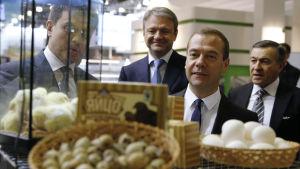 Rysslands jordbruksminister Aleksandr Tkatjev och premiärminister Dmitrij Medvedev beundrar livsmedel på jordbruksmässa i Moskva.