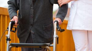 Person med rollator och person som tillhör sjukvårdspersonalen.