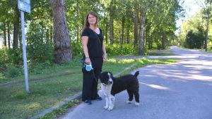 Sara Bengts står med svartvit hund i koppel vid vägen som går förbi Plagen