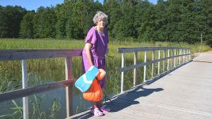 Äldre dam i badrock med simgrejer i handen står på bryggan vid Plagen