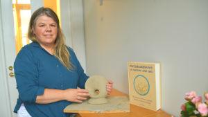 Kvinna i blått håller i rund lerfigur