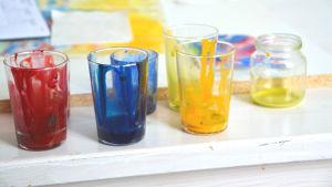 Glas med röd, blå och gul färg på en vit bordskant