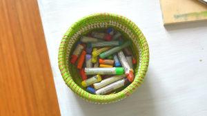 Liten grön korg med färgkritor i