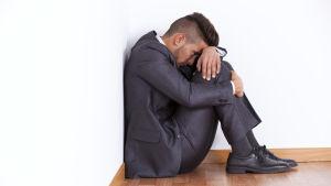 En man sitter ledsen i hörnet av ett rum.