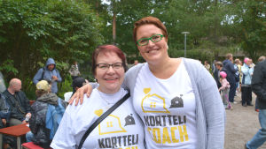 Två kvinnor står bredvid varandra och ler. Båda har på sig vita skjortor med texten korttelicoach.