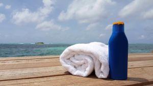 Handduk och solkräm på en brygga.