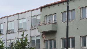 Övre delen av ett trevåningshus, en balkong som är söndervittrad undertill