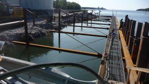Stålkonstruktioner är placerade i marken och havet vid bygget av den förlängda kajen vid yttre hamnen i Kaskö.