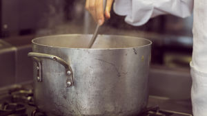 Hand rör om i soppa med en slev.