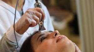 En kvinna som får behandling med microneedling - en lite dyna med massor med små nålar som gör hål på huden.
