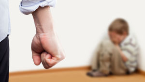 Barn kurar ihop sig i ett hörn medan en man står i förgrunden med knuten näve.